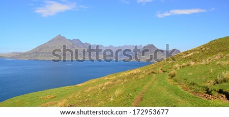 Ocean, rocky mountains, grassy hills in Scotland