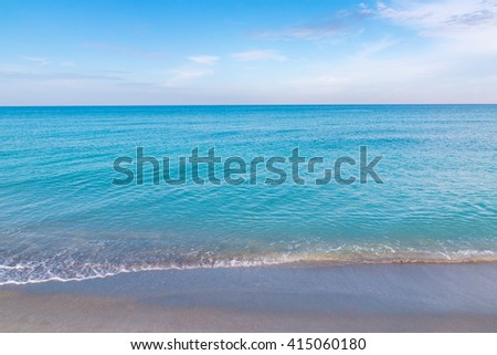 Ocean, sandy beach and blue sky at early morning - stock photo