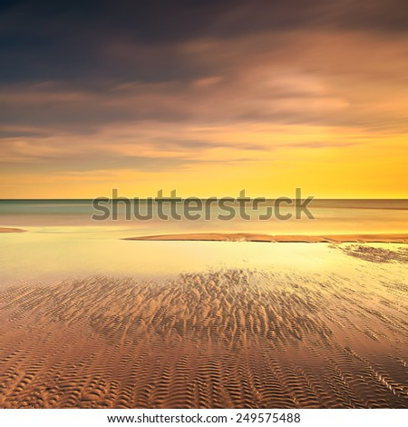 Ocean sandy beach line and warm red yellow sunset. Long exposure photography - stock photo