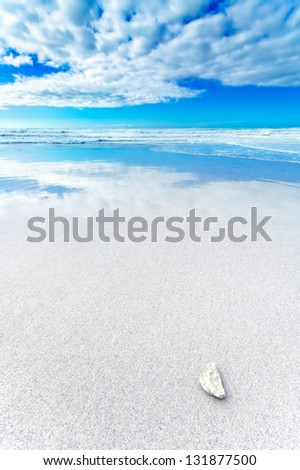 Ocean seascape. White rock or pebble in a white sandy beach under blue and cloudy sky in a bad weather. Waves on background. - stock photo