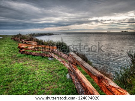 Ocean shore with wooden fence in Victoria - stock photo