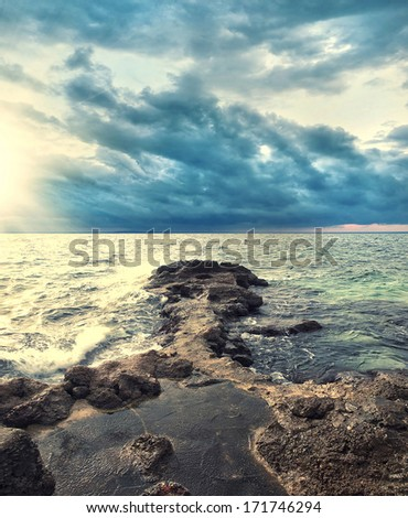 ocean storm with dramatic clouds and rocky coastline - stock photo