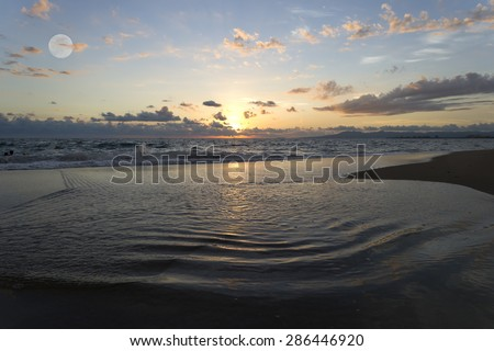 Ocean sunset landscape water ripples with moon and clouds overhead. - stock photo