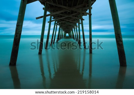 Ocean surf at the Bogue Inlet Fishing Pier, in Emerald Isle, North Carolina, is photographed with a very long exposure prior to sunrise. - stock photo