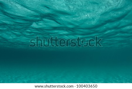 ocean surface and the sand below - stock photo