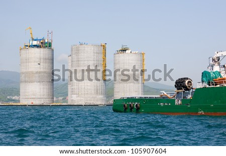 Ocean tug towing the base offshore oil drilling platform. Sea of Japan. Russian coast. - stock photo