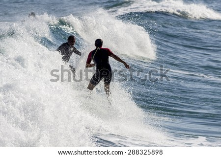 Ocean view and people surfing in Tavira Island coast beach, Algarve, Portugal. - stock photo
