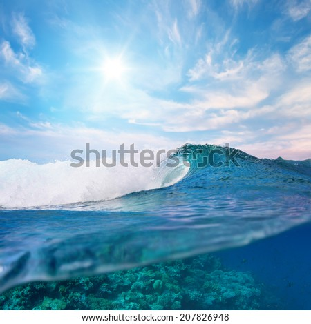 ocean view cloudy sky and breaking surfing wave splitted to two parts by waterline - stock photo