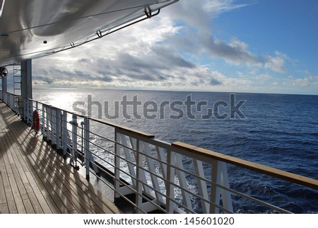 Ocean view from a cruise ship deck on a bright day with blue skies and clouds in the Pacific ocean - stock photo