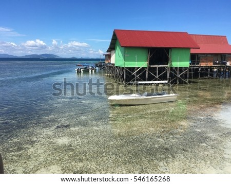 Ocean view of low tide and village house on Mabul Island in Celebes Sea, Sabah, Malaysia