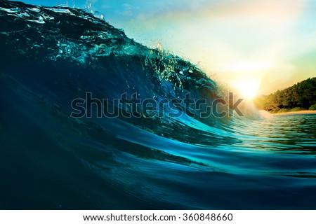 ocean-view seascape landscape Big surfing ocean wave with slightly cloudy sky and the sun - stock photo