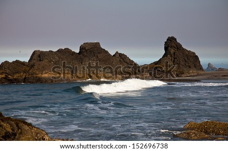 Ocean wave braking next to some rocks - stock photo
