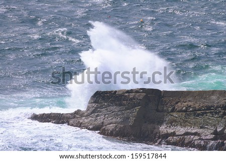 Ocean wave breaking on the rocks of the coastline. Scotland, Uk - stock photo