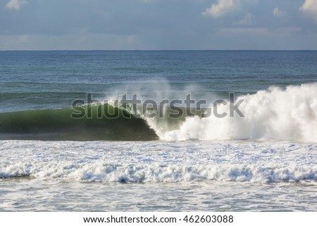 Ocean Wave Hollow Ocean Waves crashing water power along beach coastline from storm weather.