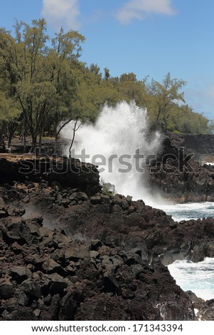 Ocean waves along the lava rock shore of Hawaii - stock photo