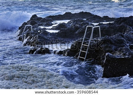 Ocean waves and stairs in public pool of Termas da Ferraria, Sao Miguel island, Azores