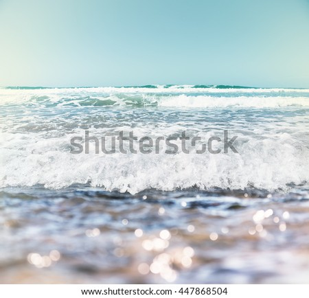 Ocean waves and surf with bokeh effects in the foreground.  Image features a pastel retro look with subtle cross-processing. - stock photo