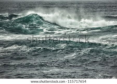 Ocean waves breaking near coastline - stock photo