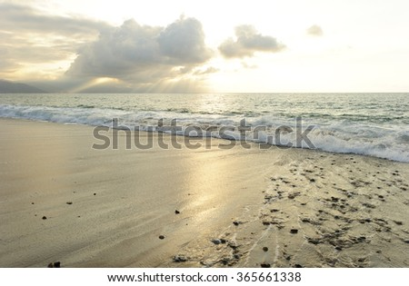 Ocean waves is brightly light golden seascape with waves rolling to the shore as scattered sunbeam break through a dramatically onto the ocean horizon. - stock photo