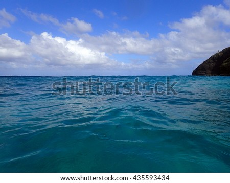 Ocean waves ripple with Makapuu Lighthouse and point in the corner looking out to sea on a wonderful day on the east side of Oahu, Hawaii. - stock photo