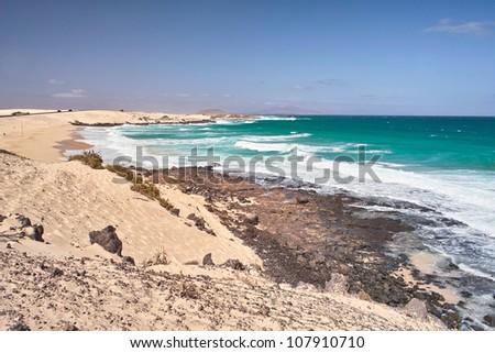 Ocean waves roll to sandy sea beach. - stock photo