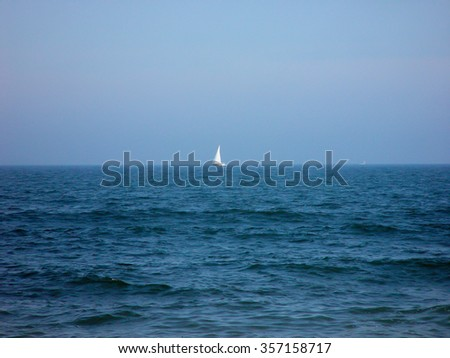 Ocean with small sail boat