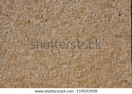 ocher stone wall with rectangular parts on a modern building - stock photo