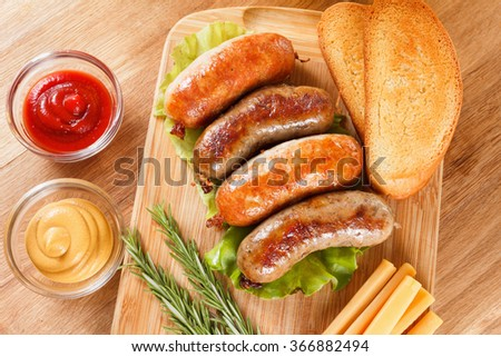 October fest traditional menu, beer and roast beef or chicken sausage  with ketchup, mustard and rosemary. Wooden cutting board - stock photo