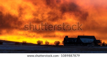 OCTOBER 9, 2017 - Home in silhouette on Hastings Mesa, Colorado with firey sunset behind it