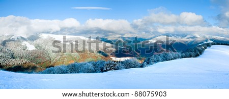 October mountain beech forest edge with first winter snow and last autumn colorful foliage on far mountainside. Two shots stitch image.