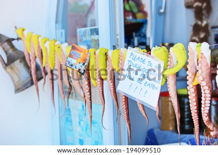 Octopus hanging on a line in front of a greek shop with note attached to the line  - stock photo