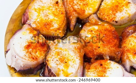 Octopus with olive oil and paprika in the foreground with the background out of focus - stock photo