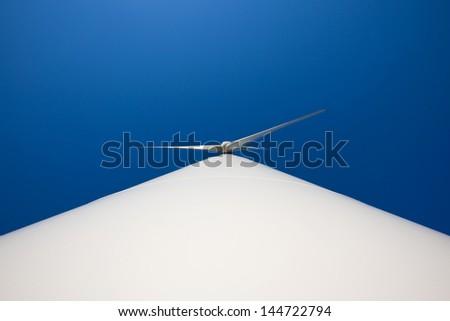 Odd angle of a wind turbine against blue sky - stock photo