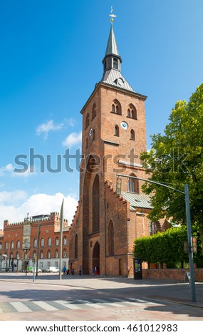Odense, Denmark - July 21, 2015: The gothic St. Canute's Cathedral with the City Hall Palace in the background