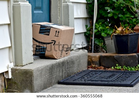 ODENTON, MD, USA - DECEMBER 22, 2015: An Amazon package sitting in front of a residential home. Amazon is the largest Internet-based retailer in the United States. - stock photo