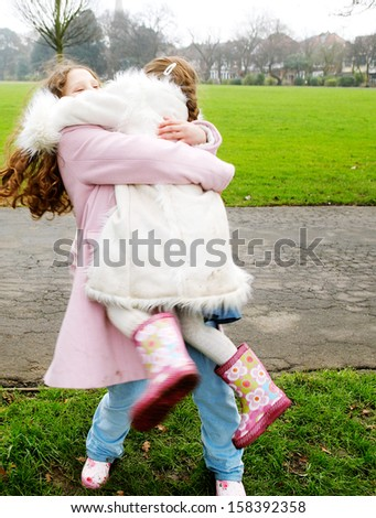 Oder sister girl carrying younger sister in her arms while turning around being playful in a green grass park during a cold winter day outdoors. - stock photo