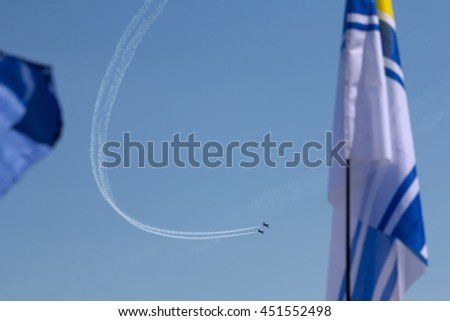 Odesa, Ukraine - July 03, 2016: Ukrainian naval forces flag and flying plane. air show during celebration of NAVY day - stock photo