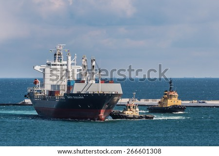 ODESSA - APRIL 04: Two tugs assisting bulk carrier ship to enter port harbor on April 04, 2015 in Odessa, Ukraine. - stock photo