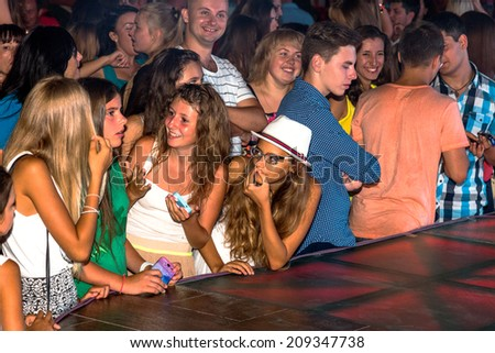 ODESSA - AUGUST 2: Nightclub. An enthusiastic crowd of spectators at the scene of a new modern entertainment shows for visitors, vacationers in  summer holiday season, August 2, 2014, Odessa, Ukraine - stock photo
