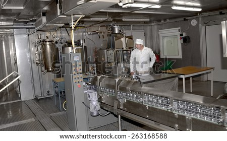 Odessa, Ukraine, April 14, 2011: Modern food processing plant produces milk. Conveyor line with bottles and cans. Workers control workflow  - stock photo
