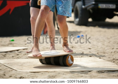 ODESSA,UKRAINE-25 AUGUST,2017:Balance board competition on the beach at summer youth festival Zgames.Young man practices balancing on board