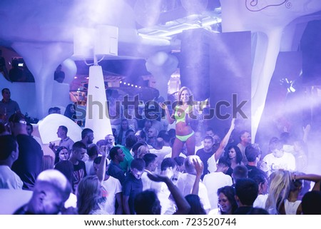 Odessa, Ukraine August 13, 2015: Ibiza Night club dj party people enjoy of music dancing sound with colorful light with Smoke Machine and lights show. Hands up in the earth.
