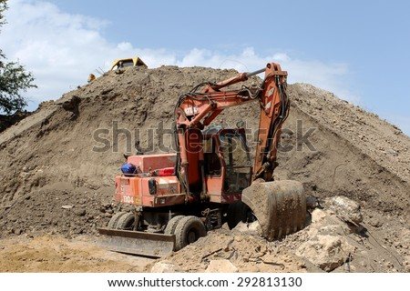 ODESSA, Ukraine August 13, 2011: Old excavator on the highway pipeline performs earthworks demolition ground leveling mountains and landscape - stock photo