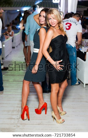 Odessa, Ukraine August 1, 2014: People smiling and posing on cam during concert in Ibiza night club party. Man and woman have fun at club. Boy and girl at night club party