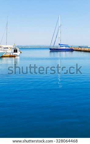 ODESSA, Ukraine - August 15, 2015: Yacht and motorboats on blue water moored to the pier. Odessa, Ukraine.