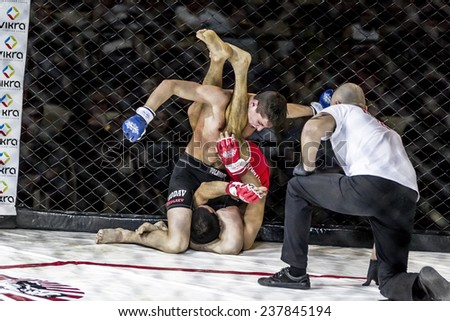 Odessa, Ukraine - December 13: Athletics MMA mixed martial arts fighters compete in the cell, causing punches and kicks. Dramatic moment of battle, December 13, 2014 in Odessa, Ukraine - stock photo