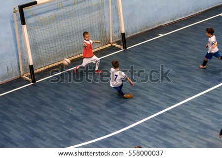 Odessa, Ukraine - December 3, 2016: Little boys, children play in mini-football in indoor sports hall at Junior championship sports city. Children sports - healthy lifestyle. Sport boy footballers
