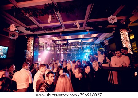 Odessa, Ukraine December 31, 2015: Night club dj party people enjoy of music dancing sound with colorful light, smoke machine, lights show and dance show. Hands up in the earth.