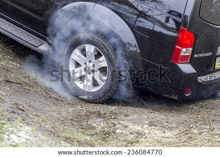 Odessa, Ukraine - December 6, 2014: Off-road 4x4 cars on the road passes sport routes in the winter mountains close-up. wheel lights up when sliding with smoke, December 6, 2014 in Odessa, Ukraine. - stock photo