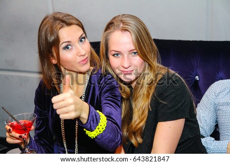 Odessa, Ukraine December 17, 2011: People drink alcohol, smiling and posing on cam during concert in night club party. Man and woman have fun at club